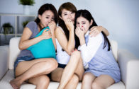 Female Friends Sitting On Sofa And Watching Horror Movie